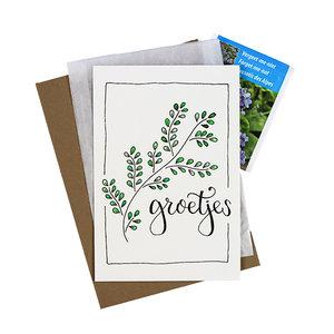 Bloemenzaden met kaart 'groetjes' verpakt in pergamijn zakje